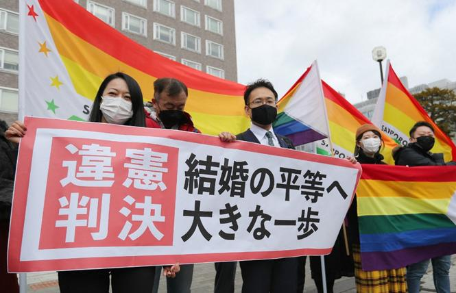 Same-sex marriage advocates celebrated outside the Sapporo District Court March 17 following a landmark ruling that Japan's denial of same-sex marriage is unconstitutional. Photo: Courtesy AFP/STR/JIJI Press