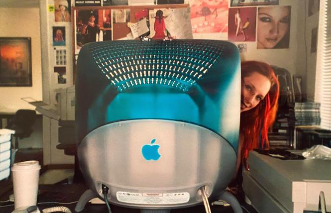 Adriana Roberts peeks out from a Mac at the B.A.R. offices, circa 2000.