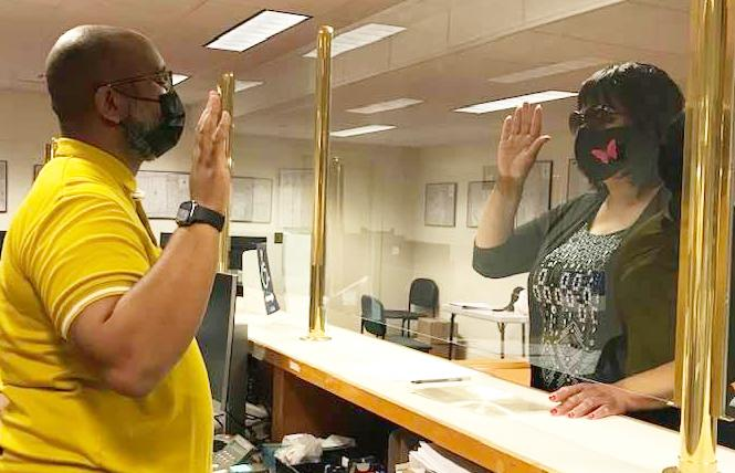 Ms. Billie Cooper, right, raises her hand after filling out paperwork at the elections department to run for District 6 supervisor. Photo: Courtesy Ms. Billie Cooper