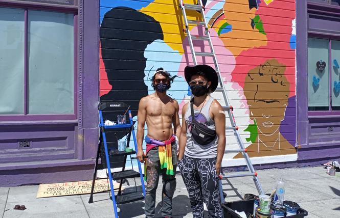Artists Juan Manuel Carmona, left, and Simón Malvaez work on their new mural on the side of the San Francisco LGBT Community Center. Photo: Scott Wazlowski