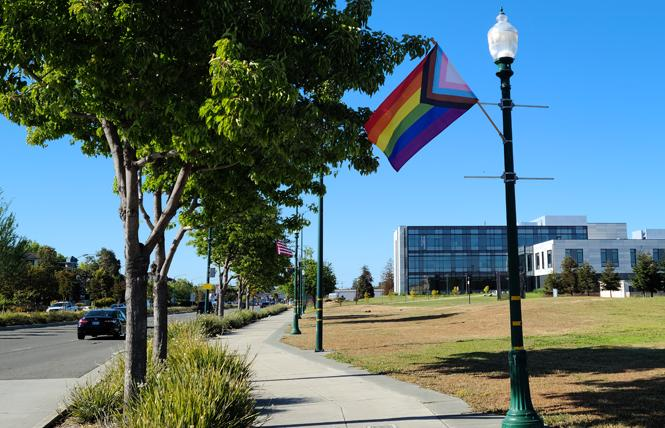 The city of Alameda recently installed Progress Pride flags, alternating with U.S. flags, along a stretch of Webster Street by the College of Alameda. Photo: Cynthia Laird
