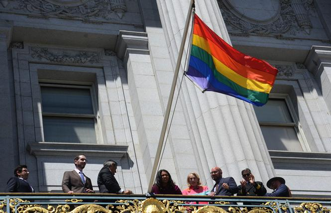 Officials stood on the Mayor's Balcony and raised the rainbow flag to celebrate the beginning of LGBTQ Pride Month and the reopening of City Hall. Photo: Rick Gerharter