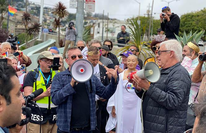 Terry Beswick, left, and Cleve Jones spoke during a rally in the Castro Friday saluting longtime ally and union member Allan Baird. Jones is holding the original bullhorn Baird gave to Harvey Milk years ago. Photo: John Ferrannini