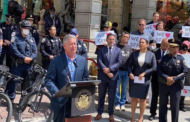 Joe D'Alessandro, at podium, joined Supervisor Ahsha Safaí, Mayor London Breed, and Police Chief William Scott to discuss an increase in patrol officers in different parts of the city during the summer travel season. Photo: John Ferrannini