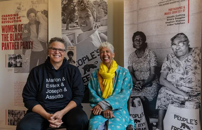 """Archivist Lisbet Tellefsen, left, with her partner and former Black Panther party leader Ericka Huggins sit in front of the exhibit showcasing women in the Black Panther Party, housed in the home of Jilchristina """"Jil"""" Vest at the corner of Center Street and Dr. Huey P. Newton Way in West Oakland. Photo: Jane Philomen Cleland"""