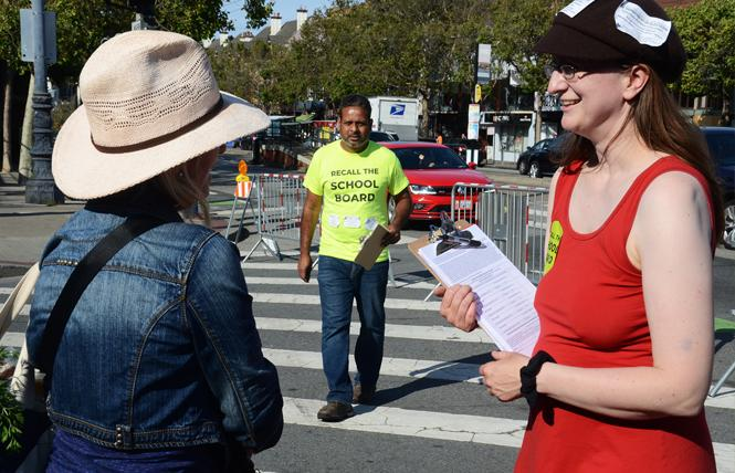 Autumn Looijen, right, asked Angela Rossoff to sign a petition to recall three members of the San Francisco School Board at the Castro Farmers Market in June. Her partner, Siva Raj, center, also was collecting signatures. Photo: Rick Gerharter