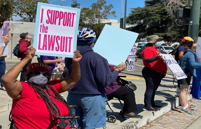 Mills College alumna Nadine Dixon, left, held a sign at a rally August 2 outside the courthouse in Oakland. Photo: John Ferrannini
