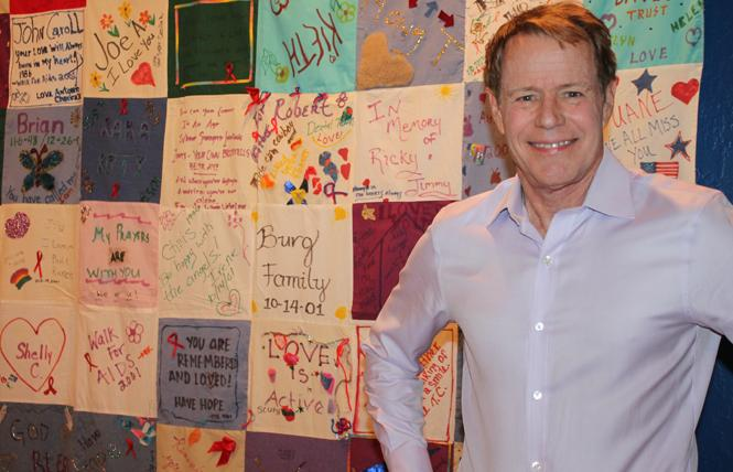 """Ken Yeager stands in front of an AIDS quilt panel on display at the """"Coming Out: 50 Years of Queer Resistance and Resilience in Silicon Valley"""" exhibit at History San Jose. Photo: Heather Cassell"""