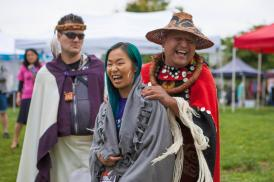 [A broadly smiling person in a button blanket and woven cedar hat places a blanket on the shoulders of a grinning, green haired person, with a festival in the background]