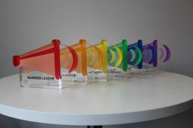 The six awards from the 2017 StandOUT Awards ceremony. Each award is a different colour of the Pride Rainbow Flag, with the awards lined up to make the rainbow.