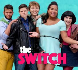 "[The cast of The Switch stands triumphant, smiling, and arms open, under words reading ""The Switch. Work. Love. Mortal Danger."" on a bright blue background.]"