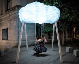 A swing topped by a large glowing cloud, shining in the night. A person in a dress sits on the swing, holding onto the ropes.