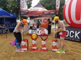Two contestants play a game pumping up balloons outside a booth with ROCK 101 branding.