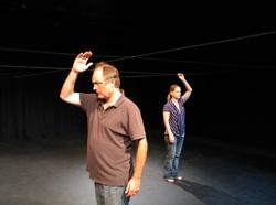 "Ron Bottitta and Kristina Llyod use an overhead line to find their way around a completely dark stage in ""More Dark"""