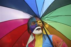 An activist with multicolored paint on her face and matching umbrella particiaptes a protest demanding equality for LGBTIQ people in Medan, North