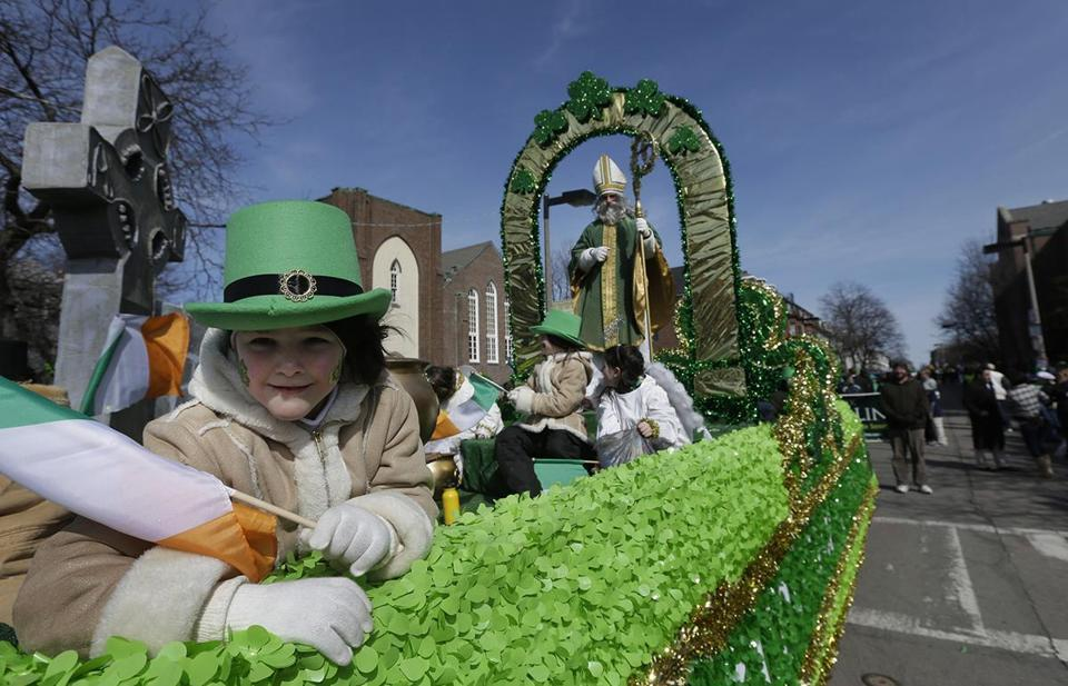 A girl held an Irish flag while in costume on a float in Southie, 2013.