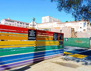 A rainbow painted fence encloses a temporary parking lot at the site of the senior housing component of the 55 Laguna housing project. Preserved structures from the old San Francisco State Teachers College and construction for new housing can be seen in the background