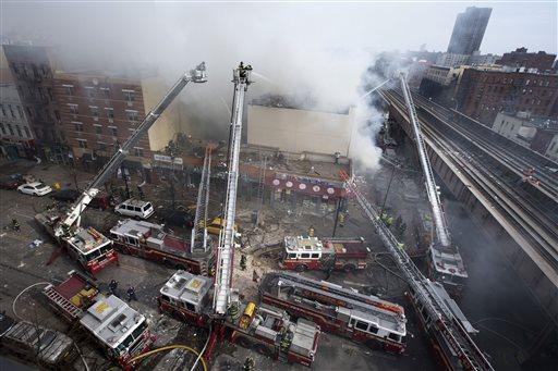 Firefighters battle a fire after a building collapses in the East Harlem neighborhood of New York.