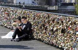 A newly wed couple rest on the Pont des Arts in Paris, Wednesday April 16, 2014