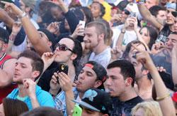 With the Colorado state capitol building visible in the background, partygoers dance and smoke pot on the first of two days at the annual 4/20 marijuana festival in Denver, Saturday April 19, 2014
