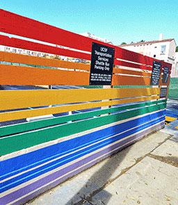 A rainbow painted fence encloses a temporary parking lot at 55 Laguna Street, site of the senior housing component of Openhouse's project.