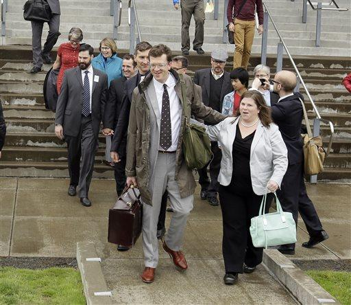 Plaintiffs, attorneys and supporters walk out of federal court where a federal judge heard oral arguments in two cases challenging Oregon's ban on same-sex marriage.