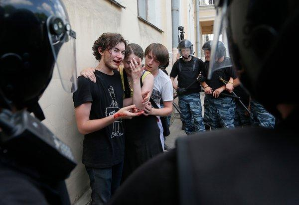 Riot police officers guarded activists who had been beaten by antigay protesters at a rally in St. Petersburg.