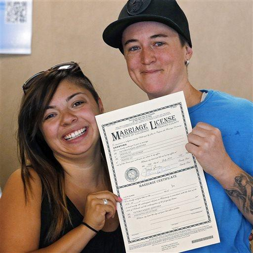 Samantha Getman, right, and Victoria Quintana show their marriage license at the Denver Clerk's office.