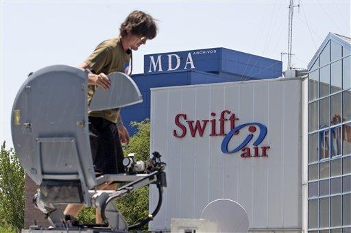 A television camera operator mounts a satellite dish on top of a van outside the Swiftair offices in Madrid, Spain.
