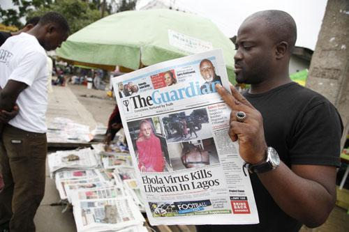 A man reads a local newspaperson a street with the headline Ebola Virus kills Liberian in Lagos, in Lagos Nigeria, Saturday, July 26, 2014