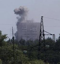 Smoke from shelling rises over a residential apartment house in Shakhtarsk, Donetsk region, eastern Ukraine on Monday, July 28, 2014. An international police team abandoned its attempt to reach the crash site of a Malaysia Airlines plane for a second day running Monday as clashes raged in a town on the road to the area.