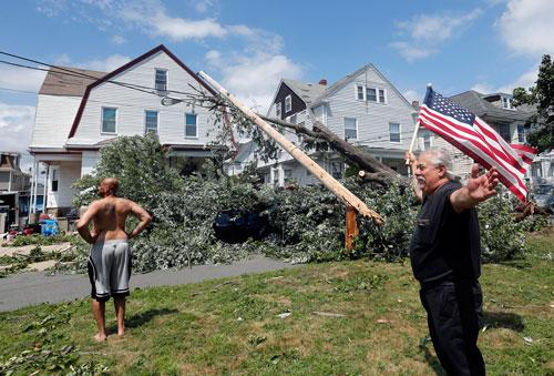 Homeowner Lenny DiBartolomeo, right, waves a flag as he and his tenant Wayne Devaughn, left, observe damage to their house in Revere, Mass., Monday, July 28, 2014, after a tornado touched down