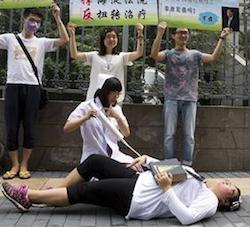 Gay rights campaigners act out electric shock treatment to protest outside a court where the first court case in China involving so-called conversion therapy is held in Beijing, China,