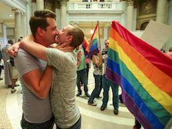Brandon Armstrong, left, and Thomas Etheridge, both of Alexander, kiss and embrace after they were wed in the rotunda of the Pulaski County Courthouse in Little Rock, Ark. Monday.
