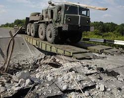 An Ukrainian government army military vehicle travels across a damaged bridge near the village of Debaltseve, Donetsk region, eastern Ukraine, Thursday, July 31, 2014.