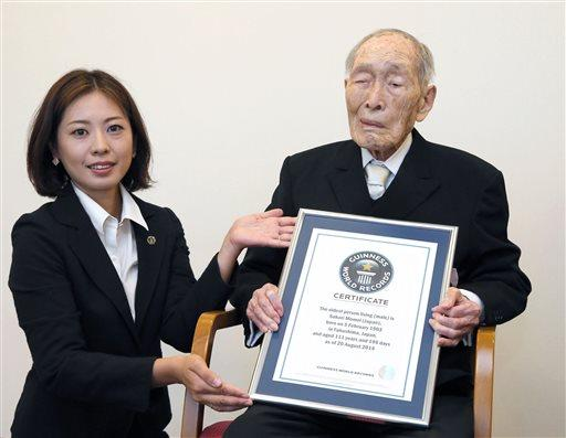 Sakari Momoi, a 111-year-old Japanese retired educator, poses for a photo after receiving a certificate from a Guinness World Records official, left.