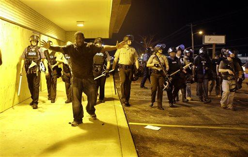 A community leader tries to get protesters to move back as police attempt to disperse a crowd in Ferguson, Mo.
