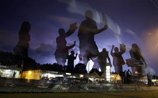Protesters march in the street as lightning flashes in the distance in Ferguson, Mo.
