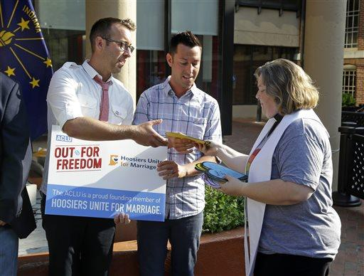Rev. Melody Merida, of the Life Journey Church, hands out signed heart-shaped cards to Greg Hasty, left, and CJ Vallero following at a rally in Indianapolis.