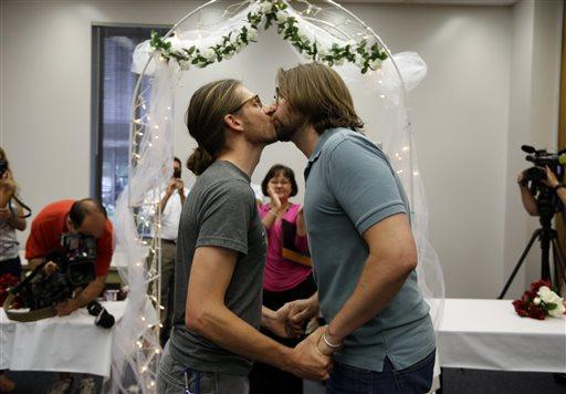 Jake Miller, left, and Craig Bowen kiss after being married by Marion County Clerk Beth White, center, in Indianapolis.
