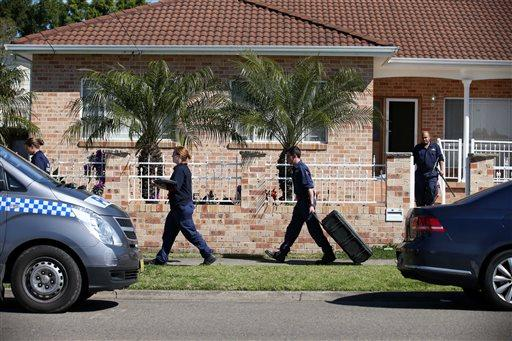 Police investigators work at a home at Guildford in suburban Sydney, Australia.
