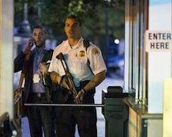 A Secret Service police officer holds a weapon as he stands near an entrance to the White House