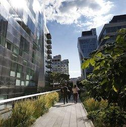 Pedestrians stroll between gleaming luxury apartment buildings along the High Line in New York, Wednesday, Sept. 17, 2014. The last stretch of the elevated walkway opens to the public Sunday, Sept. 21.