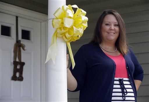 In this Aug. 20, 2014, photo, Jessica Huskey stands by a yellow ribbon placed there by her spouse Nivia Huskey before Nivia's military deployment in Jacksonville, N.C.