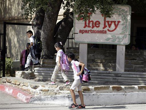 Children arriving home from school walk past the main entrance to The Ivy Apartments complex.
