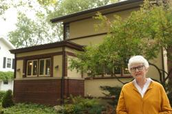 Linda McQuillen stands in front of her home designed by the famous architect Frank Lloyd Wright.