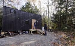 In this Tuesday, Oct. 20, 2015 photo, Hilary Lentz, of Pittsburgh, Pa., and her husband Shane leave the tiny house which they rented for a weekend in Croydon, N.H.