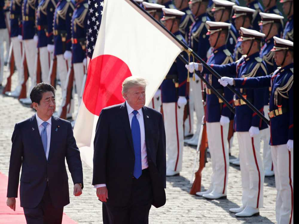 In this Nov. 6, 2017, file photo, U.S. President Donald Trump, second from left, reviews an honor guard during a welcome ceremony, escorted by Japanese Prime Minister Shinzo Abe at Akasaka Palace in Tokyo